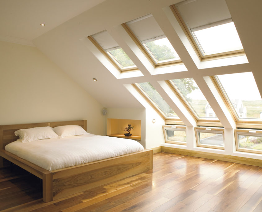 A Velux loft conversion with wooden floors, a large oak bed and windows spanning the length of the roof