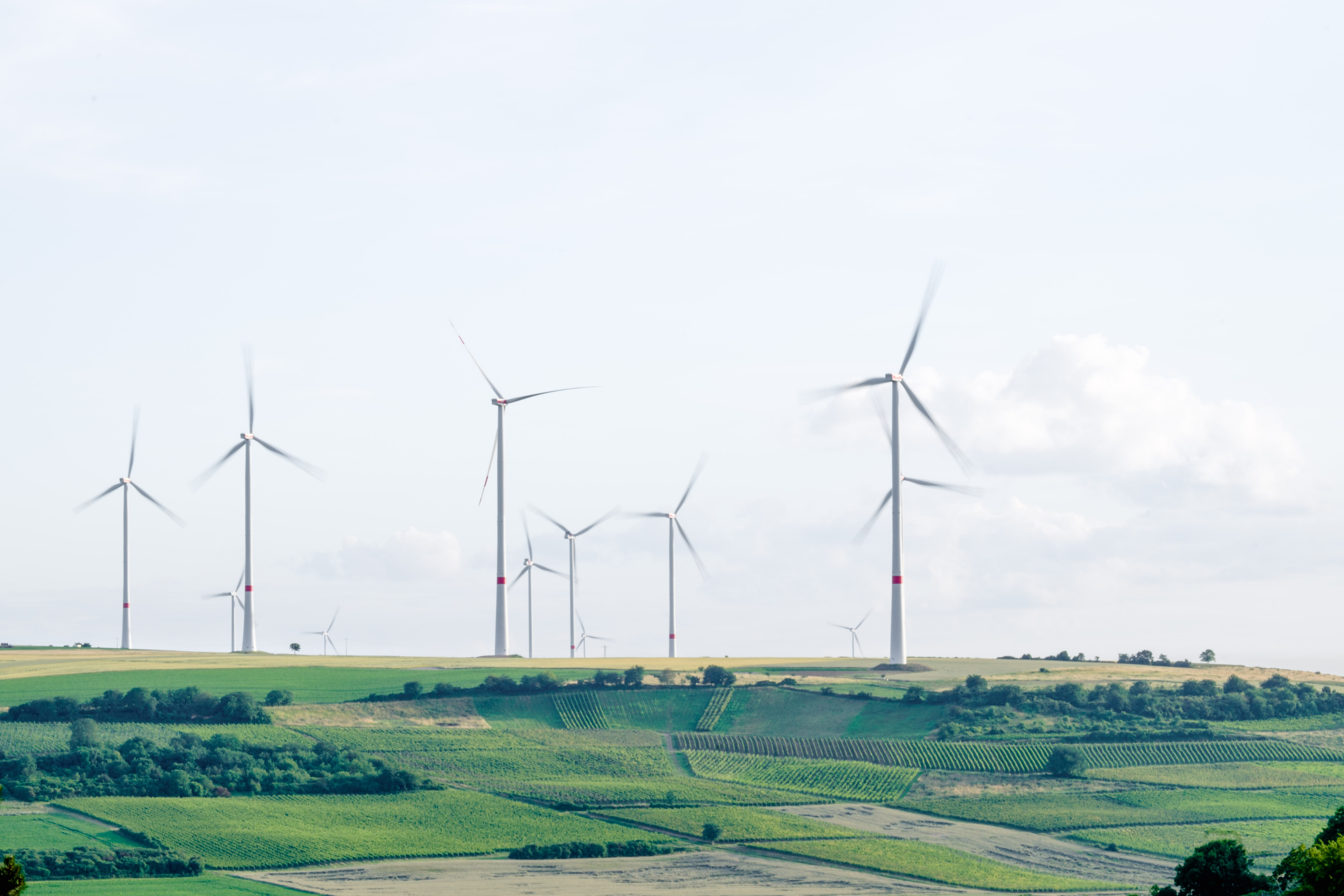 A group of wind turbines in a hilly landscape