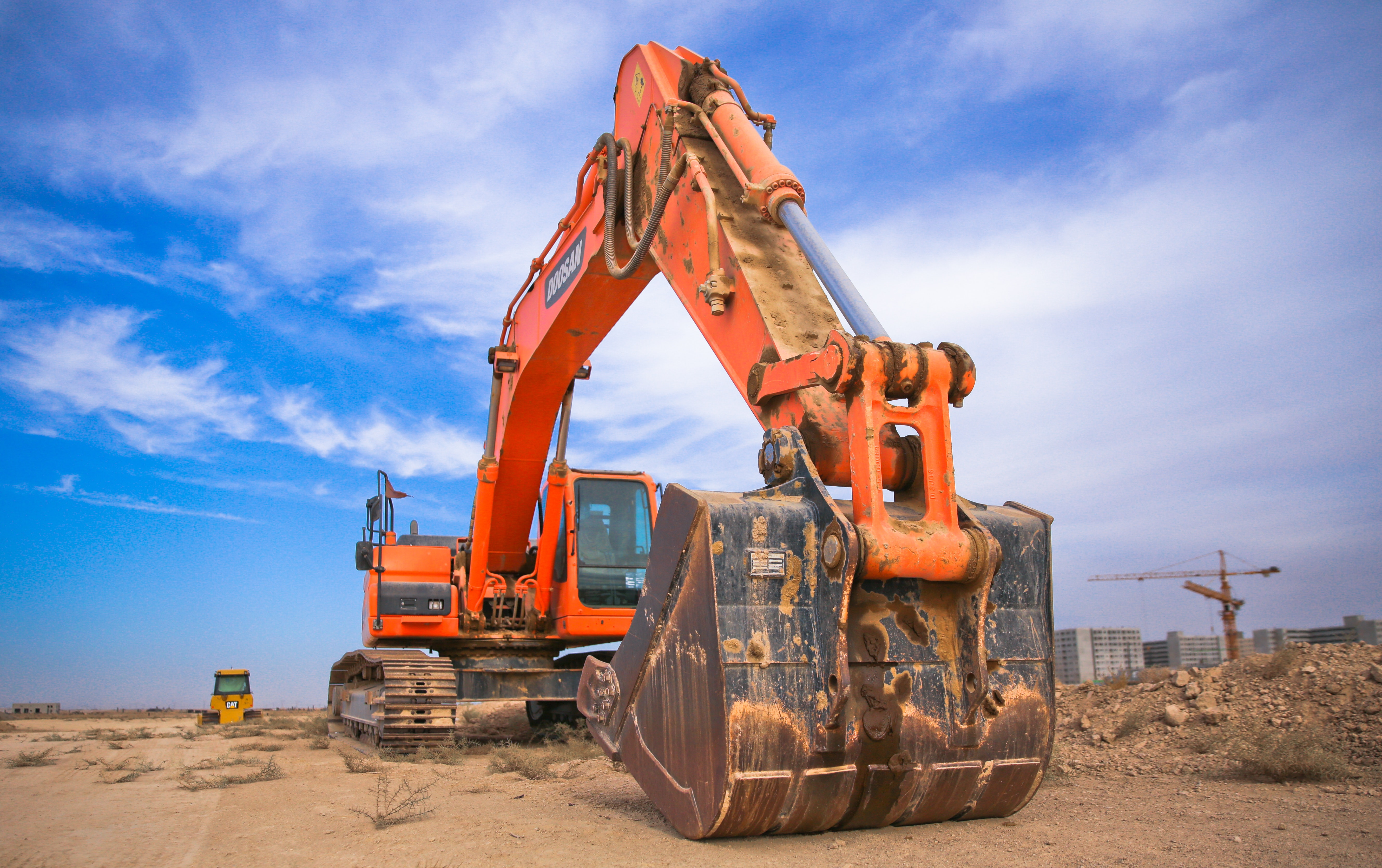 Orange excavator on a building site-vehicles such as this are a risk to health and safety in construction