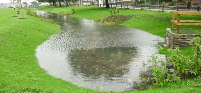 A large pool of rain water that has accumulated on a sustainable drainage system near a residential area