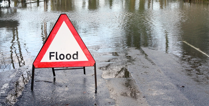 A red and white flood warning sign in the middle of a flooded street