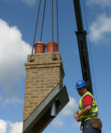 A prefabricated chimney stack being lowered onto the roof of a house