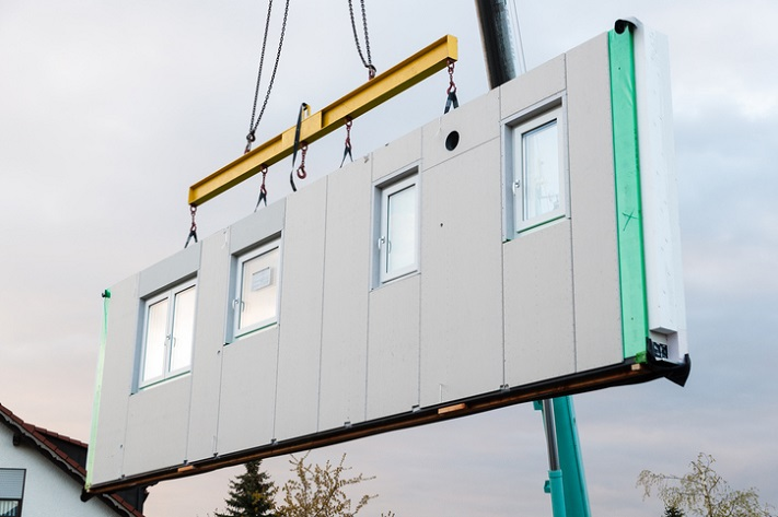 A prefabricated housing panel, featuring windows, being lowered into position by a crane