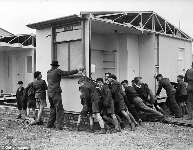 Post World War 2 school boys helping to move a section of a prefabricated house into position