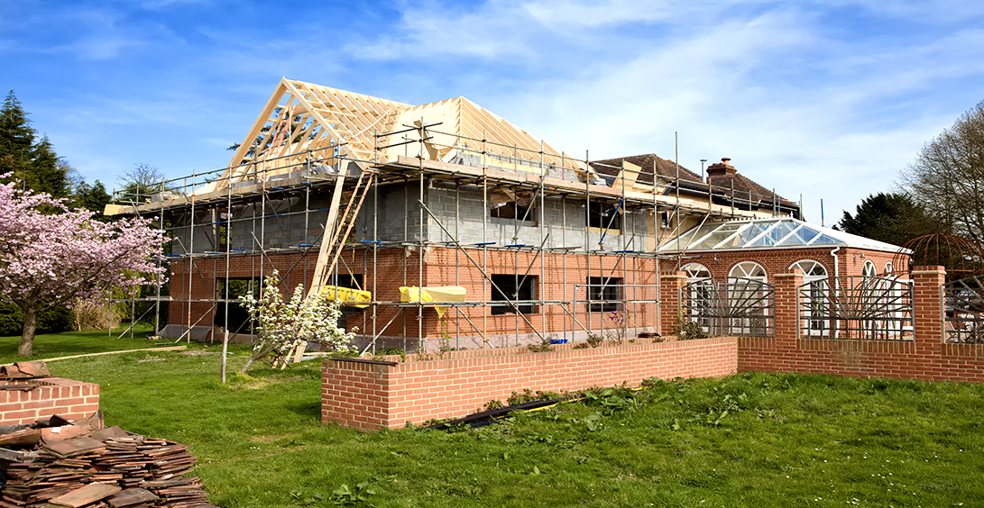 An image of a house under construction, featuring a conservatory extension.