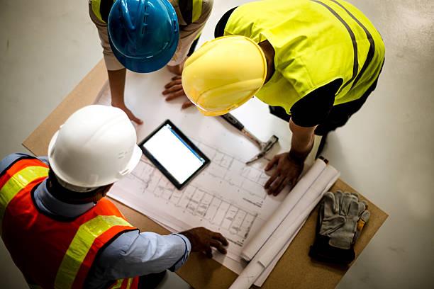 A CDM principal designer overseeing construction blueprints