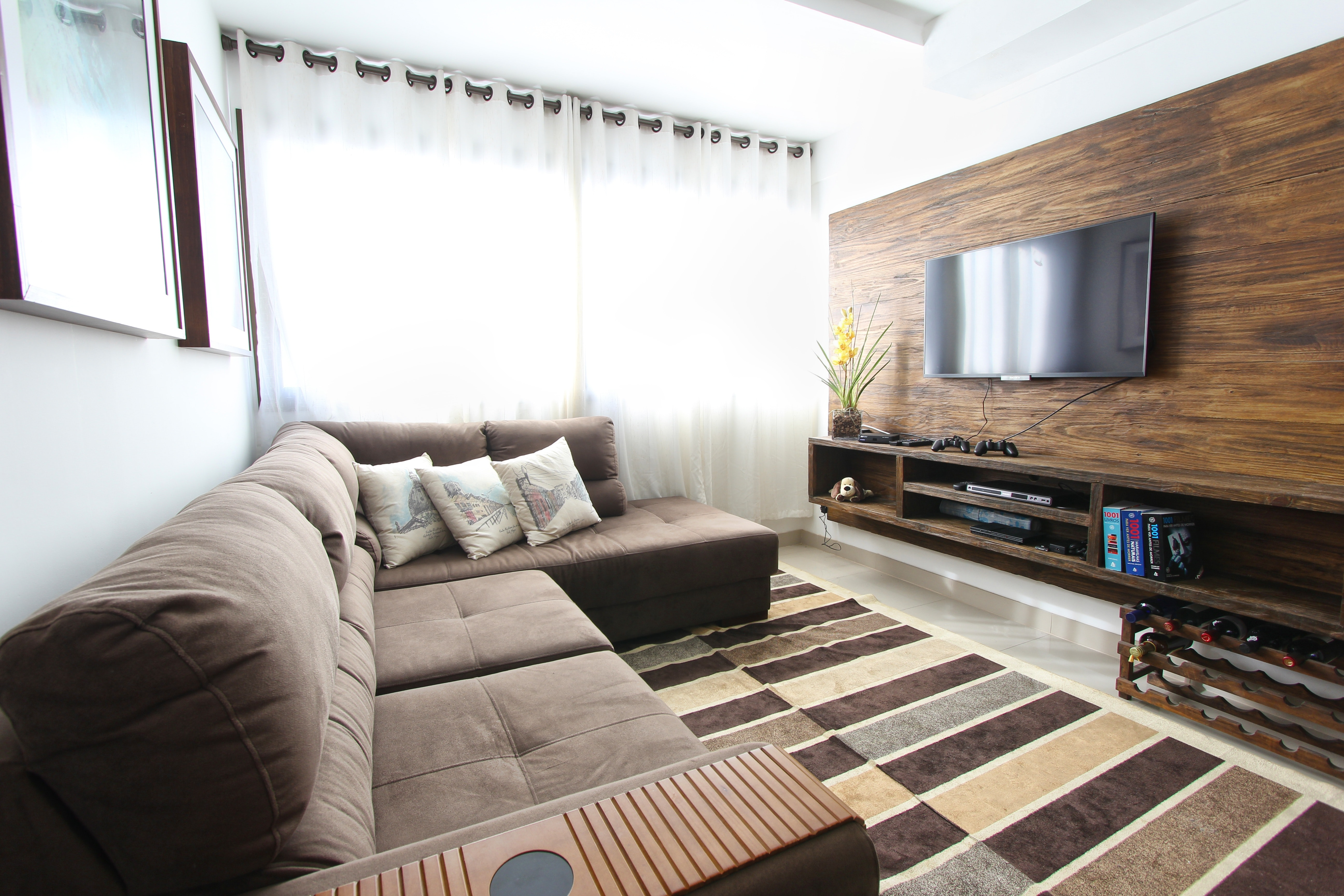 Garage converted into a living room with a TV on the wall and a large L-shape sofa