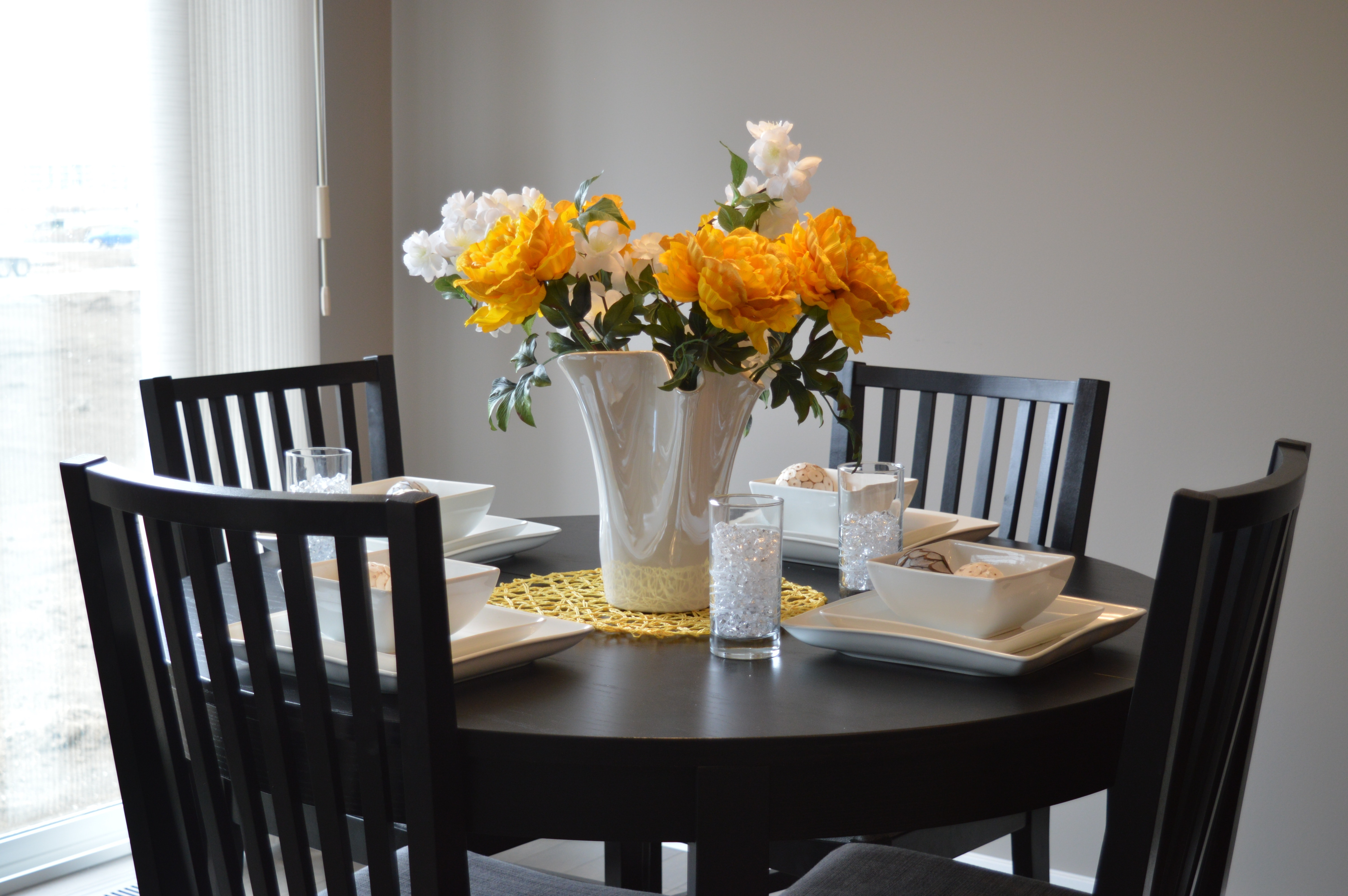 Dining table and chairs featuring flowers and dinner plates