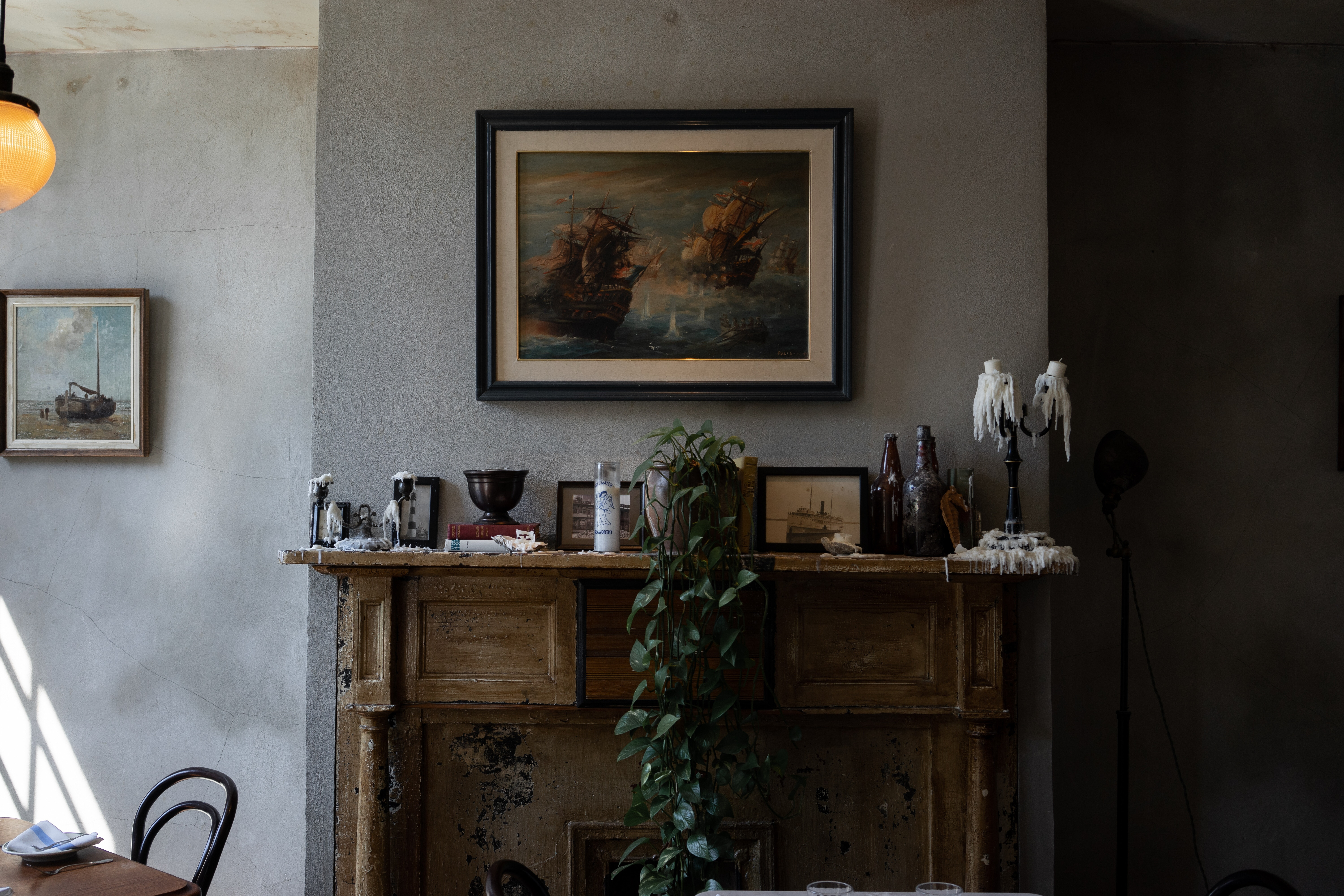 A traditional fireplace and chimney breast surrounded by ornaments, candle sticks and picture frames