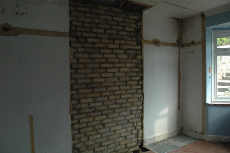 Living room with the chimney breast removed and filled in with bricks